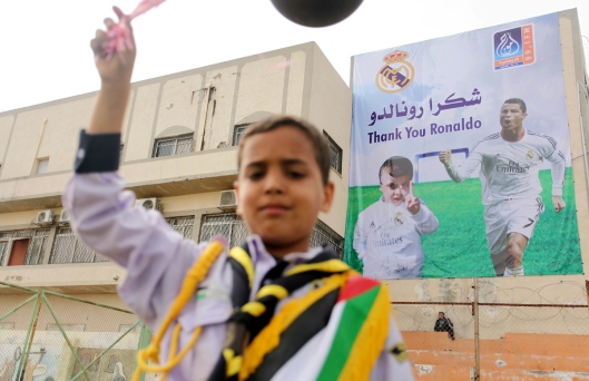 Palestinian chlidren hold ballons and posters bearing a portrait of Palestinian boy Ahmed Dawabsha, 5, who suffered severe burns in an arson attack by suspected Jewish attackers on his family home last July and in which his younger brother, Ali, and his p